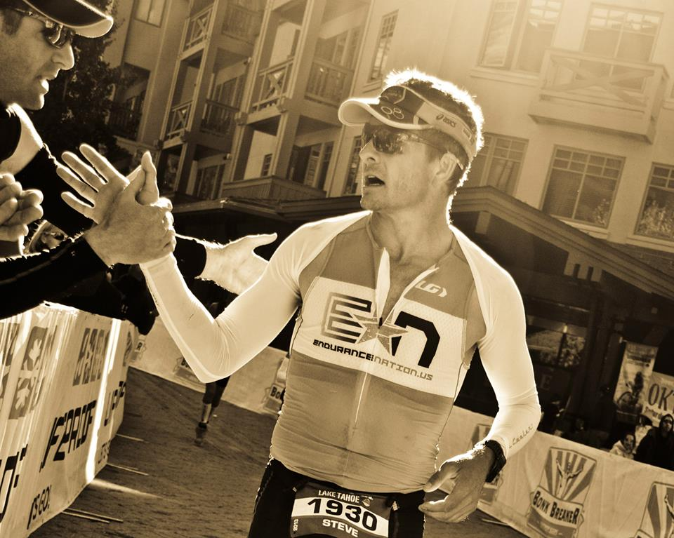 Steve Hall high fives a spectator during 2013 Ironman® Lake Tahoe